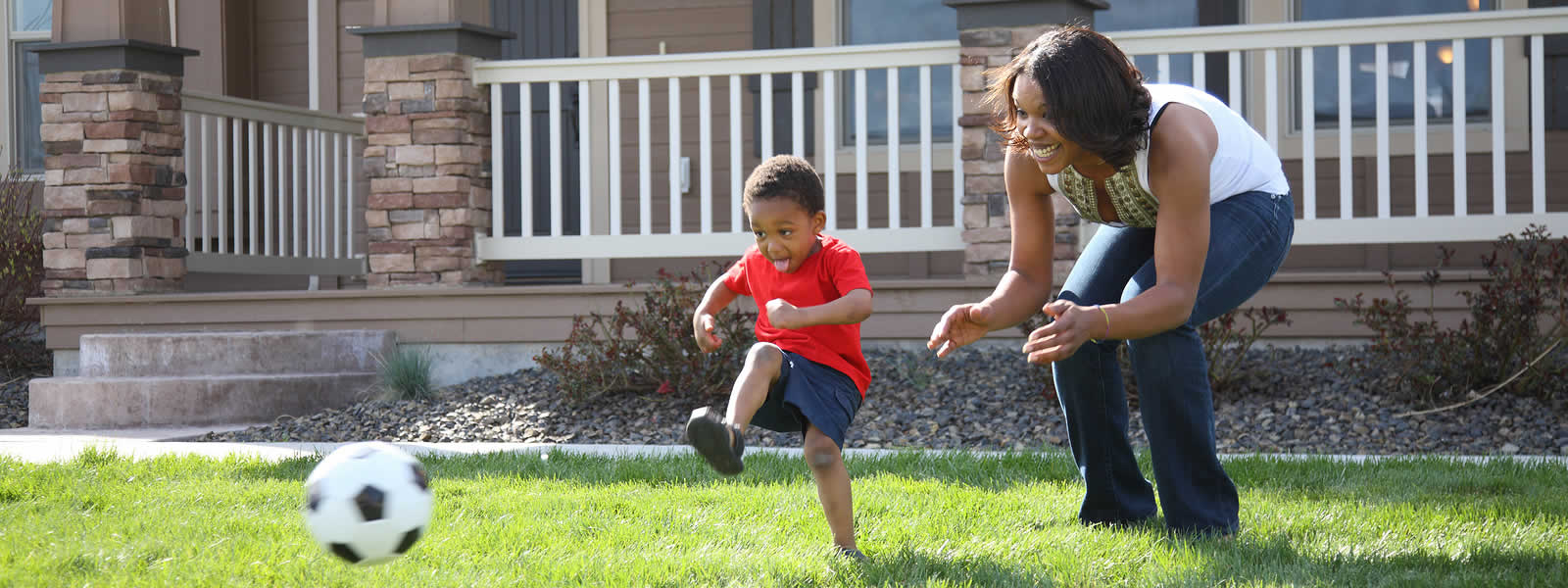 Child and mother playing soccer in front of their new home.