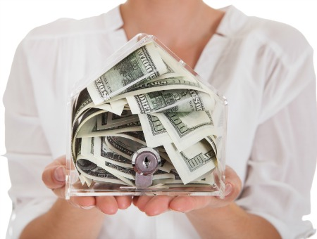 woman holding money in house-shaped box